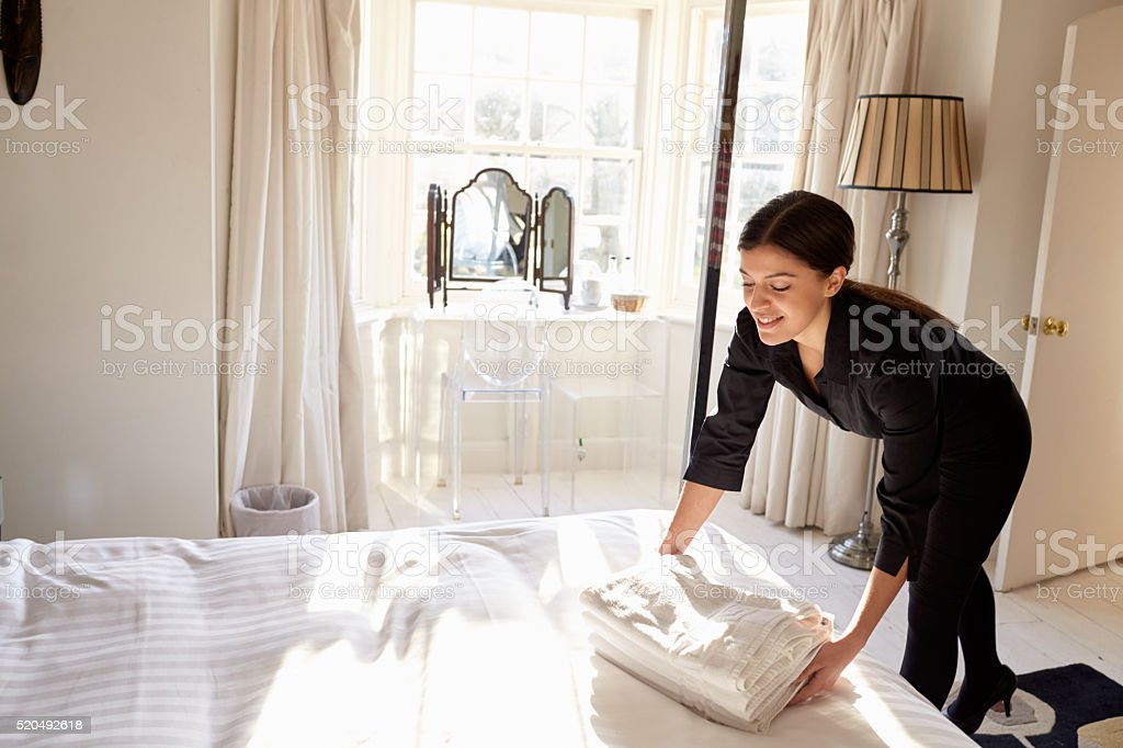 Chambermaid placing fresh linen on to a bed in a hotel stock photo