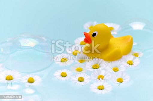 istock chamomile bath with soap bubbles, a yellow duck toy and flowers 1039604728