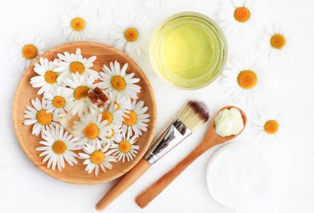 kamillenblüten und extrahierten kosmetikprodukte draufsicht. - makeup selbst gemacht stock-fotos und bilder