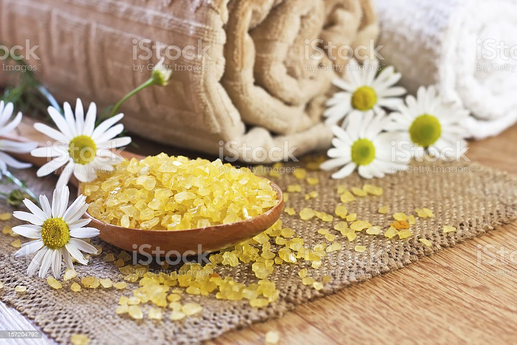 chamomile salt in wooden spoon and roller towels royalty-free stock photo