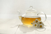 Chamomile tea in a transparent teapots and white daisy flowers on a white wooden board background.Organic teas for health