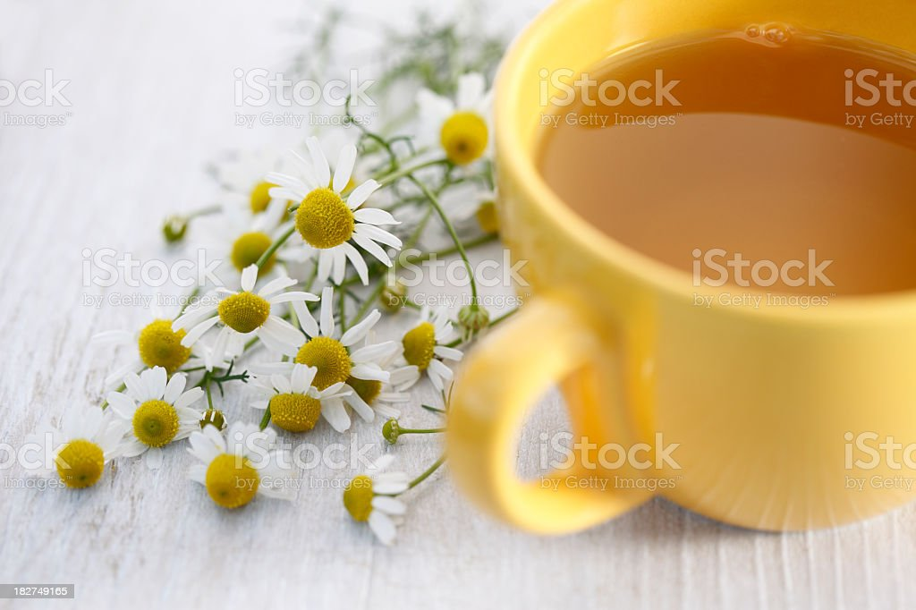 Chamomile tea in a yellow cup on white table with daisies stock photo