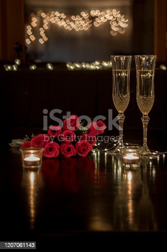 Champagne and roses on dark table for romantic dinner date night heart bokeh, vertical format