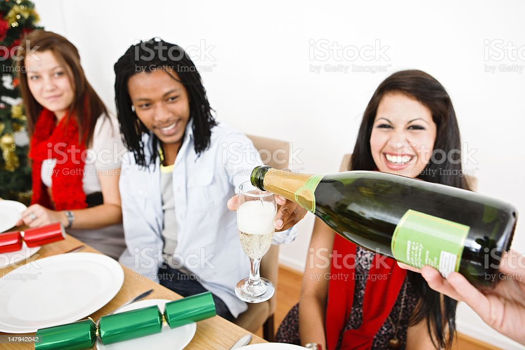 Champagne being poured for happy guests at Christmas dinner party royalty-free stock photo