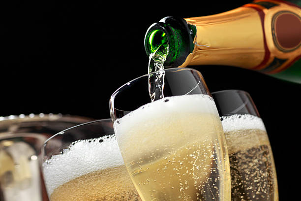 champagne being poured into champagne glasses - decant stock pictures, royalty-free photos & images