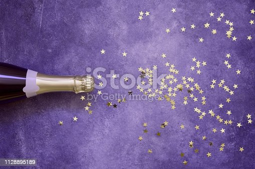 istock Champagne bottle and confetti stars on ultra violet background. Copy space,top view. Flat lay 1128895189