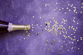 Champagne bottle and confetti stars on ultra violet background. Christmas, birthday, carnival or wedding concept. Flat lay style. Copy space. Color of the year 2019.