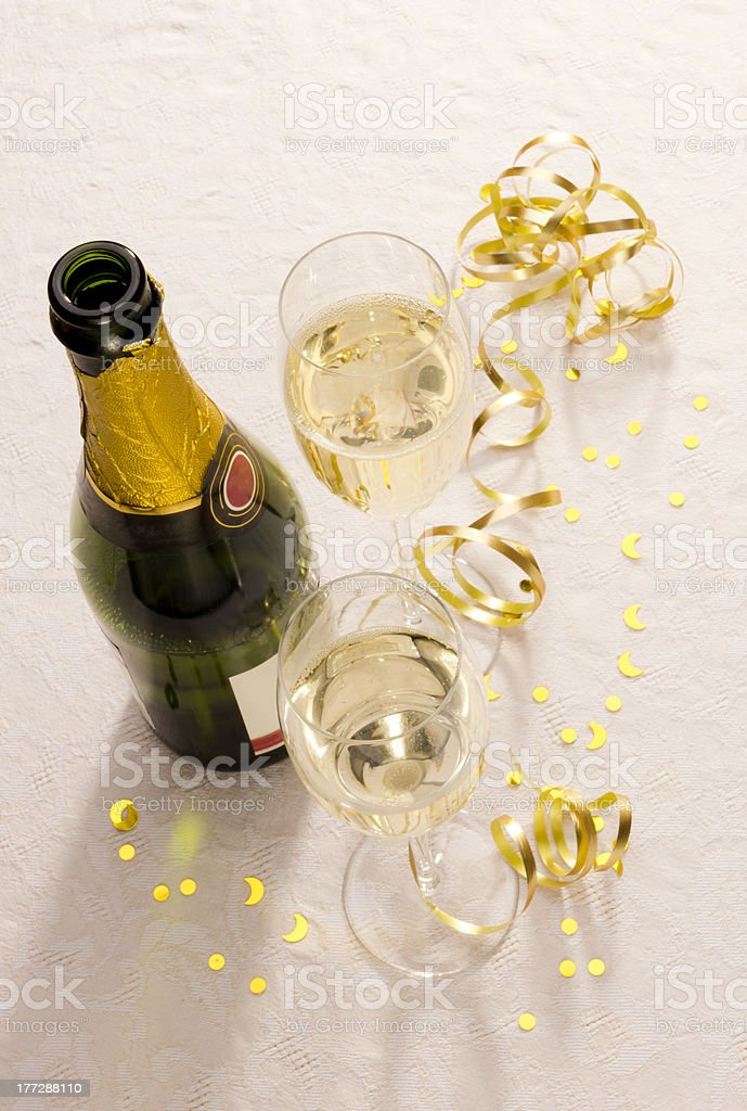 Champagne bottle and two glasses on party table royalty-free stock photo