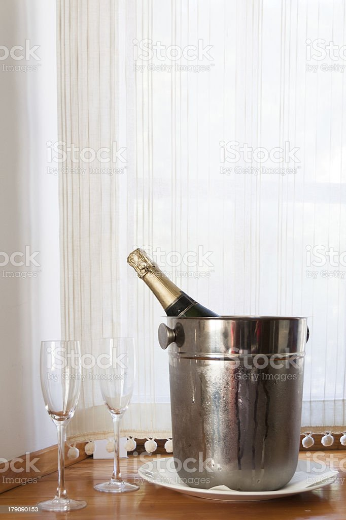 Champagne bottle in bucket with ice and two glasses royalty-free stock photo