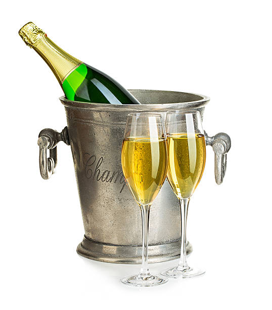 Champagne bottle in ice bucket with glasses of champagne . stock photo