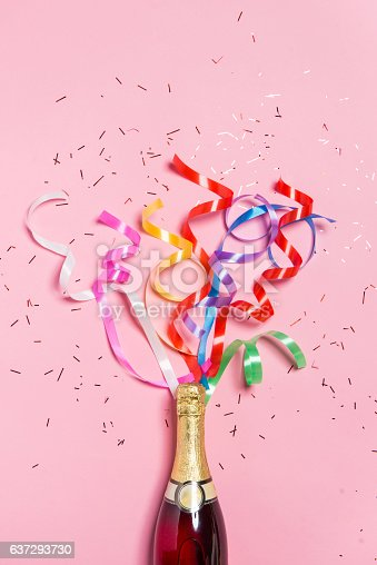 istock Champagne bottle with colorful party streamers on pink background. 637293730