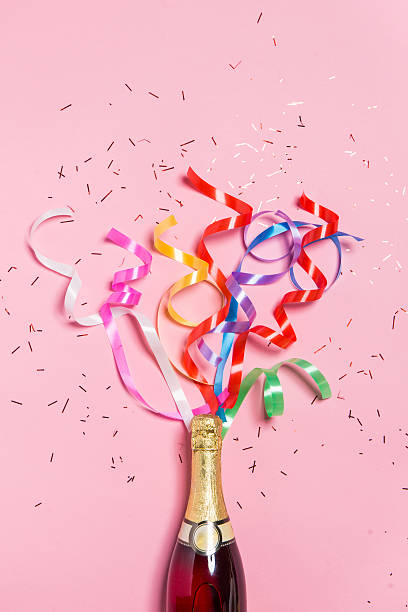 champagne bottle with colorful party streamers on pink background. - anniversary stock photos and pictures