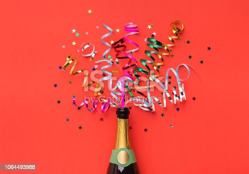 istock Champagne bottle with colorful streamers top view 1064493988