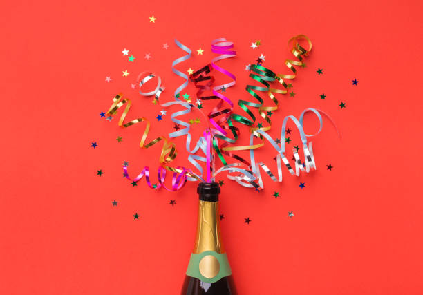 Champagne bottle with colorful streamers top view Champagne bottle with colorful party streamers on red background carnival celebration event stock pictures, royalty-free photos & images