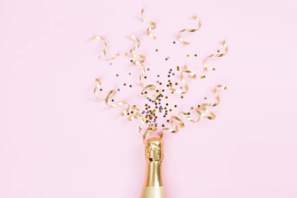champagne bottle with confetti stars and party streamers on pink background. christmas, birthday or wedding concept. flat lay. - флэтлей стоковые фото и изображения