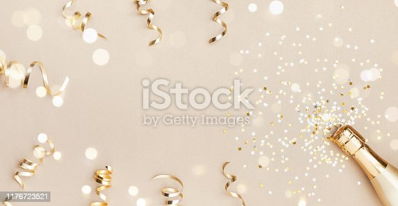 istock Champagne bottle with confetti stars, bokeh decoration and party streamers on golden background. Christmas, birthday or wedding concept. Flat lay. 1176723521