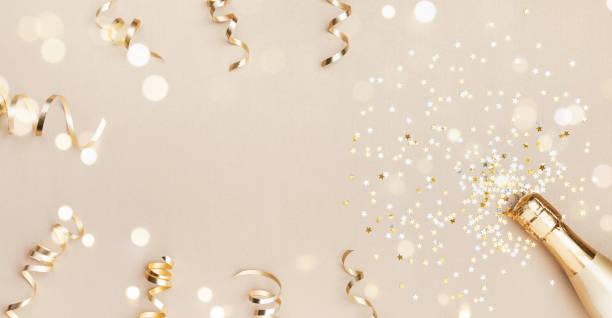 botella de champán con estrellas de confeti, decoración bokeh y serpentinas de fiesta sobre fondo dorado. concepto de navidad, cumpleaños o boda. estaba plano. - año nuevo fotografías e imágenes de stock