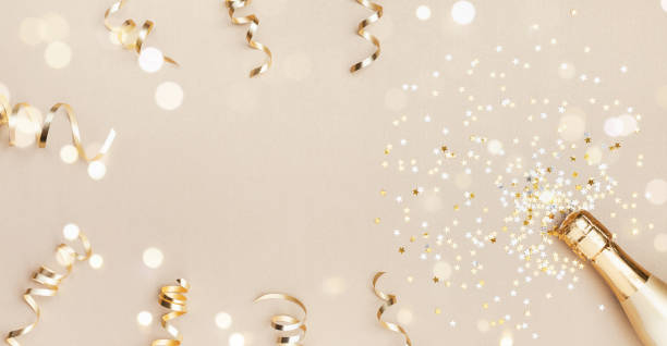 champagne bottle with confetti stars, bokeh decoration and party streamers on golden background. christmas, birthday or wedding concept. flat lay. - new year imagens e fotografias de stock
