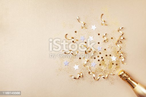 istock Champagne bottle with confetti stars, glitter and party streamers on golden background. Christmas, birthday or wedding concept. Flat lay concept. 1169145566