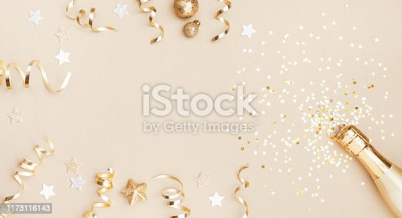 Champagne bottle with confetti stars, holiday decoration and party streamers on gold festive background. Christmas, birthday or wedding concept. Flat lay style.