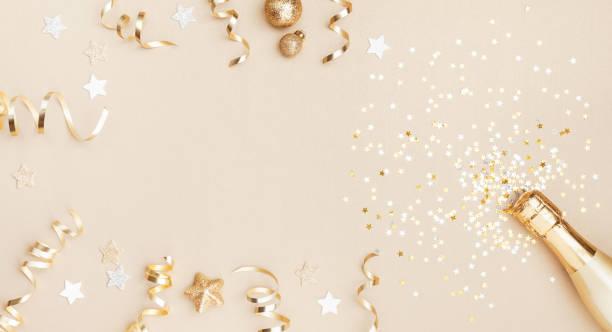 champagnerflasche mit konfetti-sternen, weihnachtsdekoration und party-streamer auf goldenem festlichem hintergrund. weihnachten, geburtstag oder hochzeit konzept. flach liegen. - originelle geburtstagsgeschenke stock-fotos und bilder