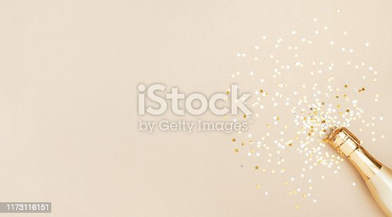 Champagne bottle with confetti stars on golden festive background. Christmas, birthday or wedding concept. Flat lay style.