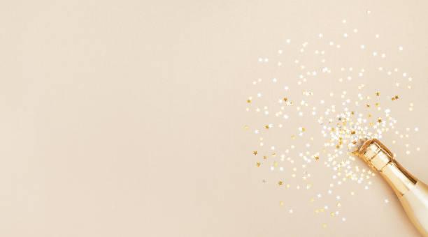 champagnerflasche mit konfetti-sternen auf goldenem festlichem hintergrund. weihnachten, geburtstag oder hochzeit konzept. flach liegen. - originelle geburtstagsgeschenke stock-fotos und bilder
