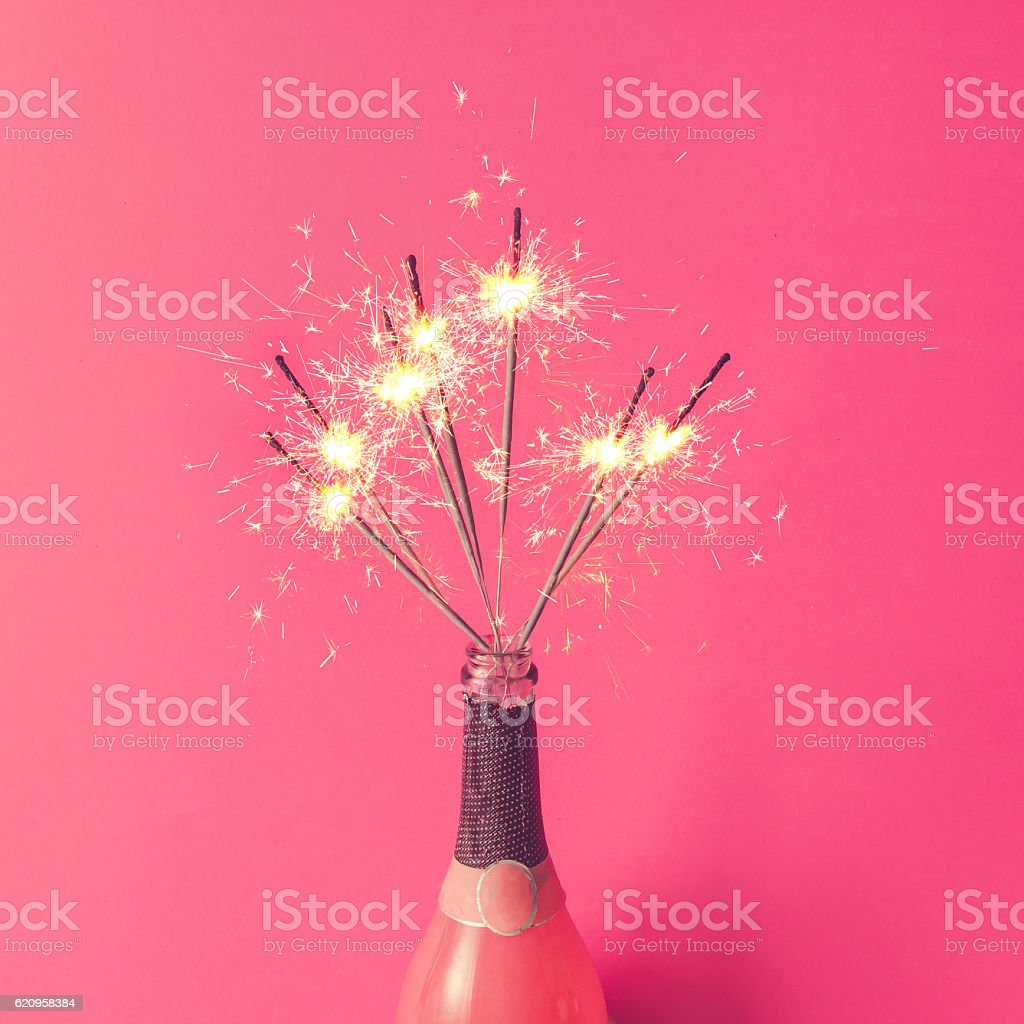 Champagne bottle with sparklers on pink background. Flat lay. – Foto