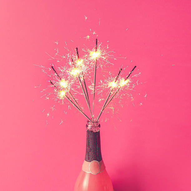 Champagne bottle with sparklers on pink background. Flat lay. stock photo