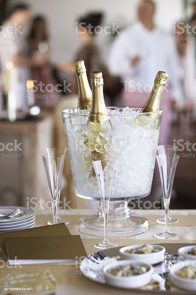 Champagne bottles in ice bucket with glasses, people in background. royalty-free stock photo