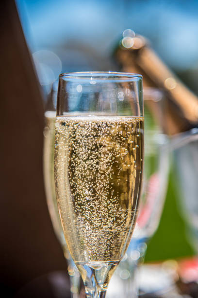 Champagne bubbles in glass in sunlight Champagne glass macro closeup with bubbles at outdoor wedding epernay stock pictures, royalty-free photos & images