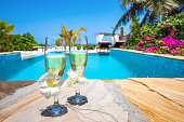 Close-up of two champagne glasses by the pool.