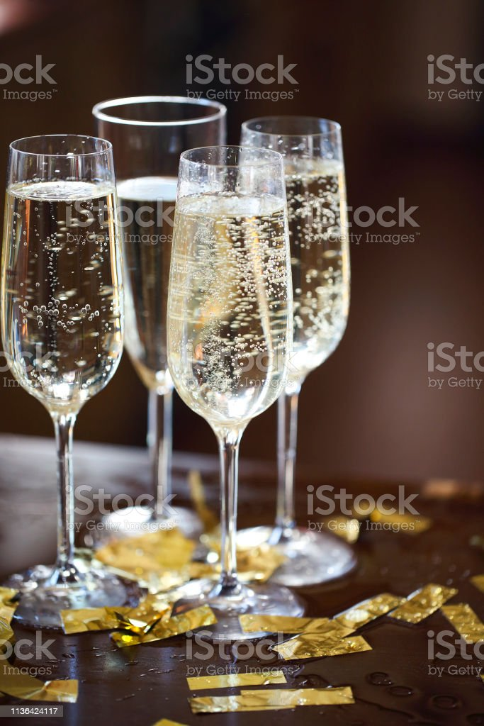 Champagne Flutes In Golden Sparkle Background with golden confetti....