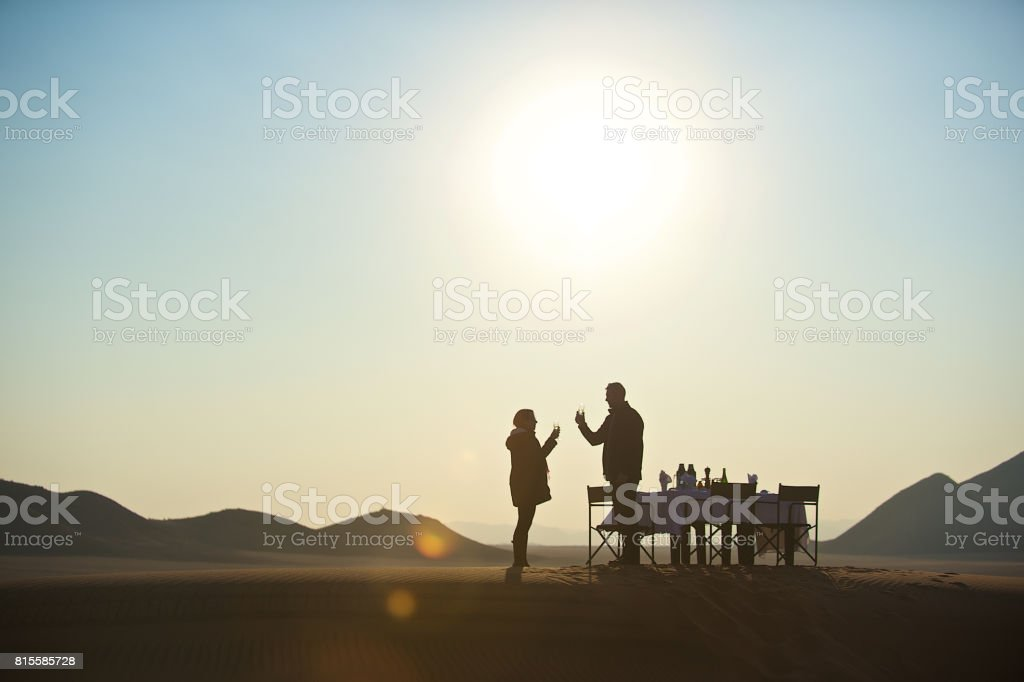 Champagne for two on sand dune stock photo