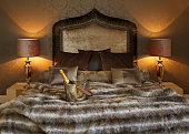 an ice bucket with two glasses and a bottle of champagne on ice, set on a luxurious bed dressed in a \