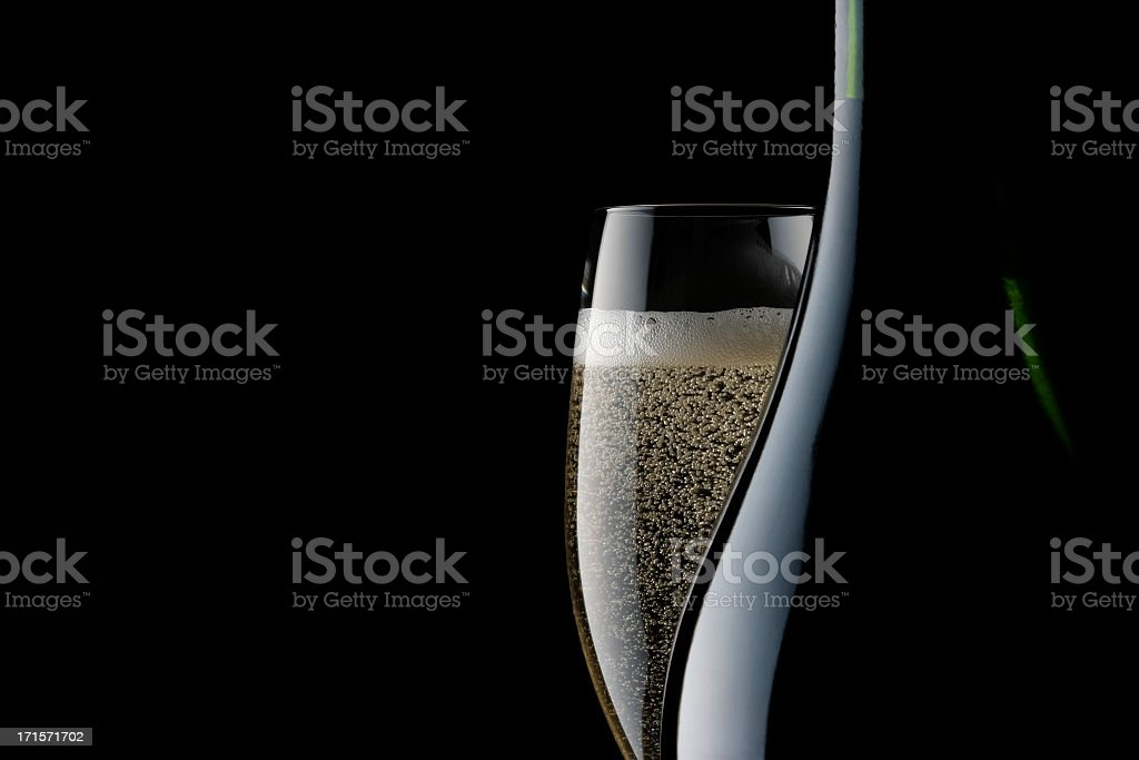 Champagne glass and blank bottle against black background stock photo