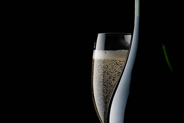 champagne glass and blank bottle against black background - champagne stock pictures, royalty-free photos & images