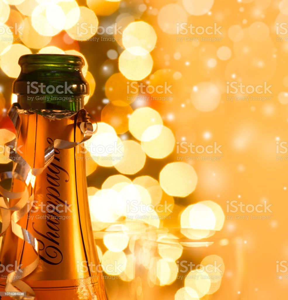 Champagne Glass And Bottle In Front Of Christmas Tree And Snowflakes stock photo