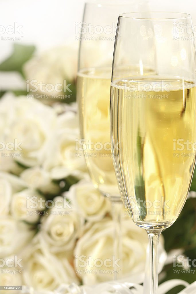 Champagne glass close-up with a bouquet of roses royalty-free stock photo