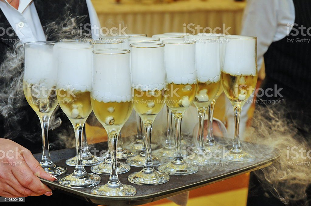 Champagne glass with carbonic ice on a tray stock photo