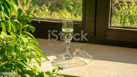 istock A champagne glass with champagne and a second glass lying on the windowsill in the sunshine 1063314174