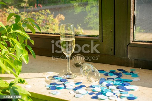 istock A champagne glass with champagne and a second glass lying on the windowsill with blue confetti 1063314138