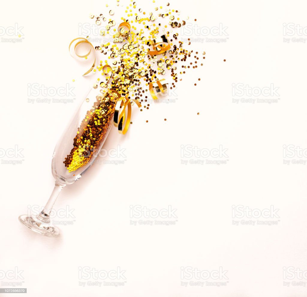 Champagne glass with golden glitter on pink background. Flatlay. Copy space. New Year concept stock photo