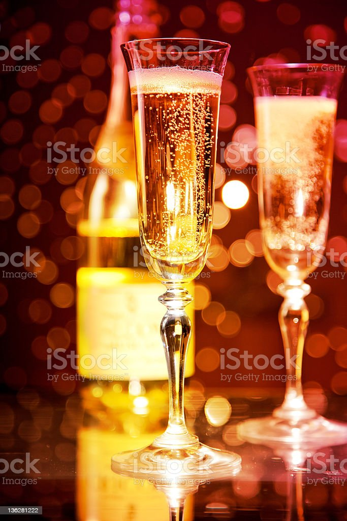 Champagne glasses and bottle Champagne glasses and bottle over holiday bokeh background, focus on first glass, perfect for holidays Alcohol - Drink Stock Photo