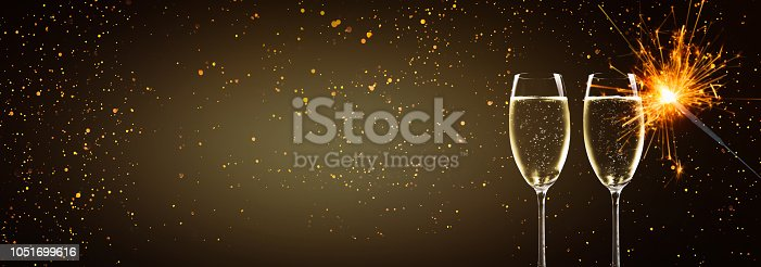 1051699126 istock photo champagne glasses and sparkler in the night 1051699616