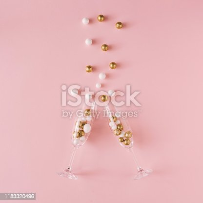 873264516 istock photo Champagne glasses filled with golden and white glitter decoration and pink background. 1183320496