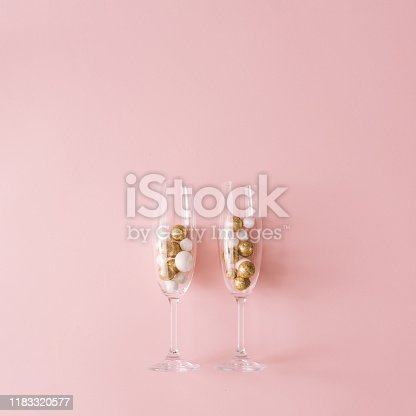873264516 istock photo Champagne glasses filled with golden and white glitter decoration and pink background. 1183320577