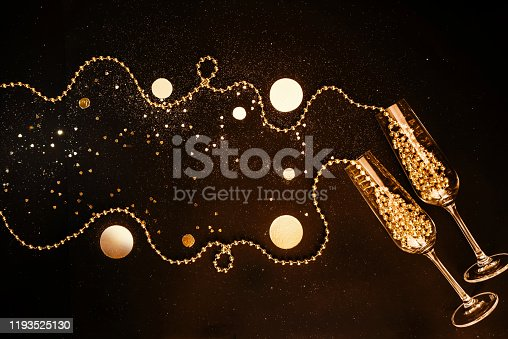 873264516 istock photo Champagne glasses filled with golden decorations on a black shiny background. Celebration minimal Christmas party. Poster Copy Space. Flat lay 1193525130