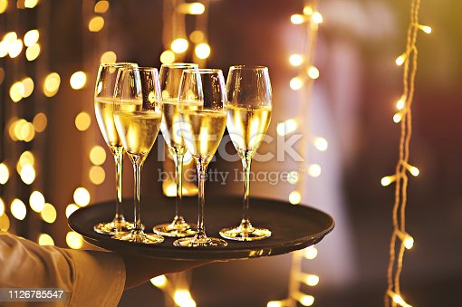 istock Champagne glasses on a tray with fairy string lights backdrop 1126785547