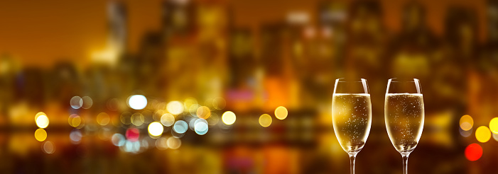 istock champagne glasses on blurred city background 1038657450